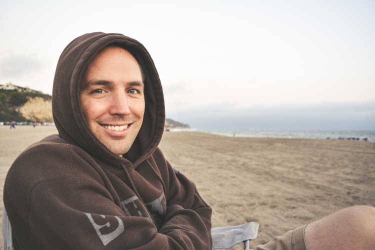 man in brown hoodie smiling at beach